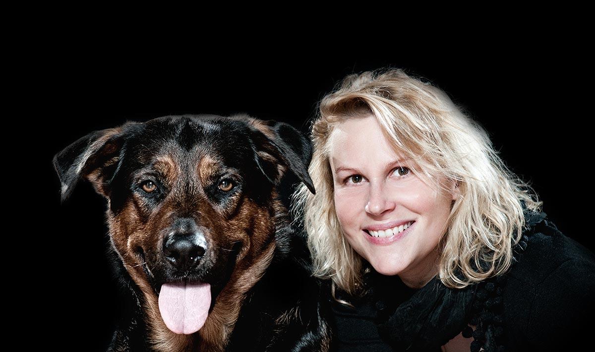 Thierphysiotherapie, Titelbild Kontakt. Nina Groth mit Hund vor schwarzem Hintergrund